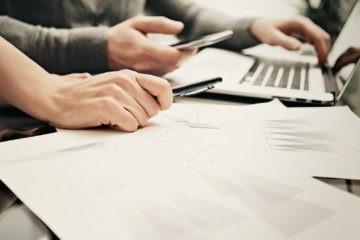 documentos e computador em cima da mesa