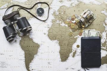 imposto de renda no mundo - mapa mundi com bússola e carteira de dinheiro