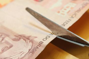 Parcelamento do Imposto de Renda - nota de real sendo cortada com uma tesoura