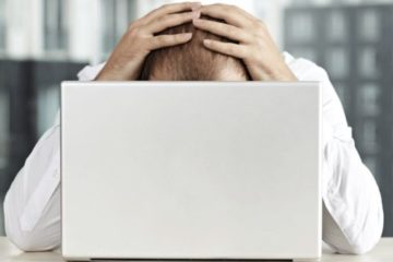 como saber se caí na malha fina - homem ansioso com as mãos na cabeça de frente pro computador